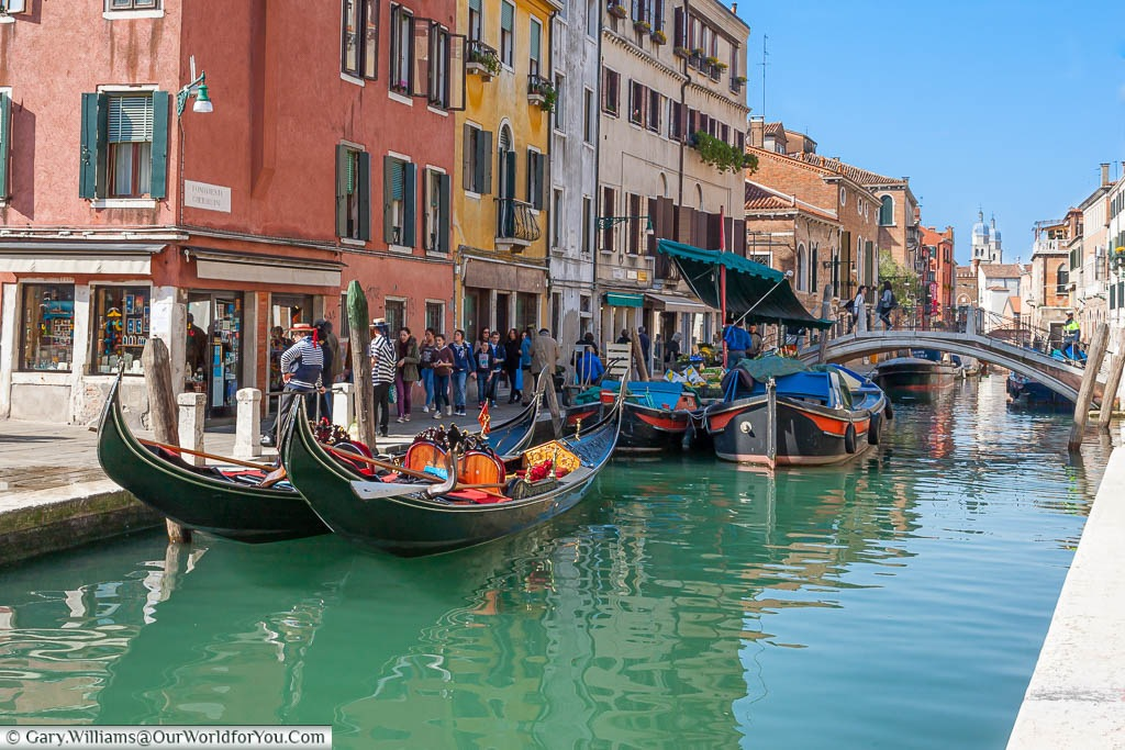 A pair of gondolas and the fruit & vegetable barge by the Ponte dei Pugni or Bridge of fists in Venice