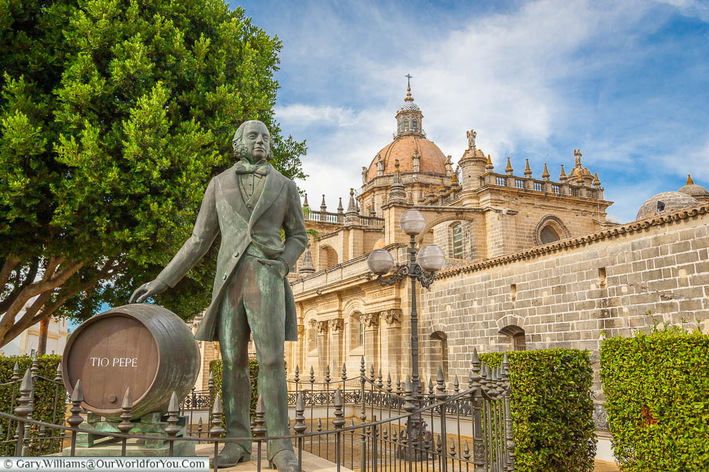 A brass statue to Tio Pepe, standing next to a sherry barrel bearing his name, with a view of Jerez Cathedral in the background.