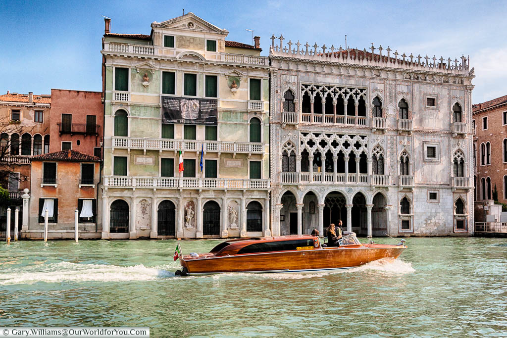 A beautiful wooden veneered water taxi in front of the Venetian palace of Ca' d'Oro