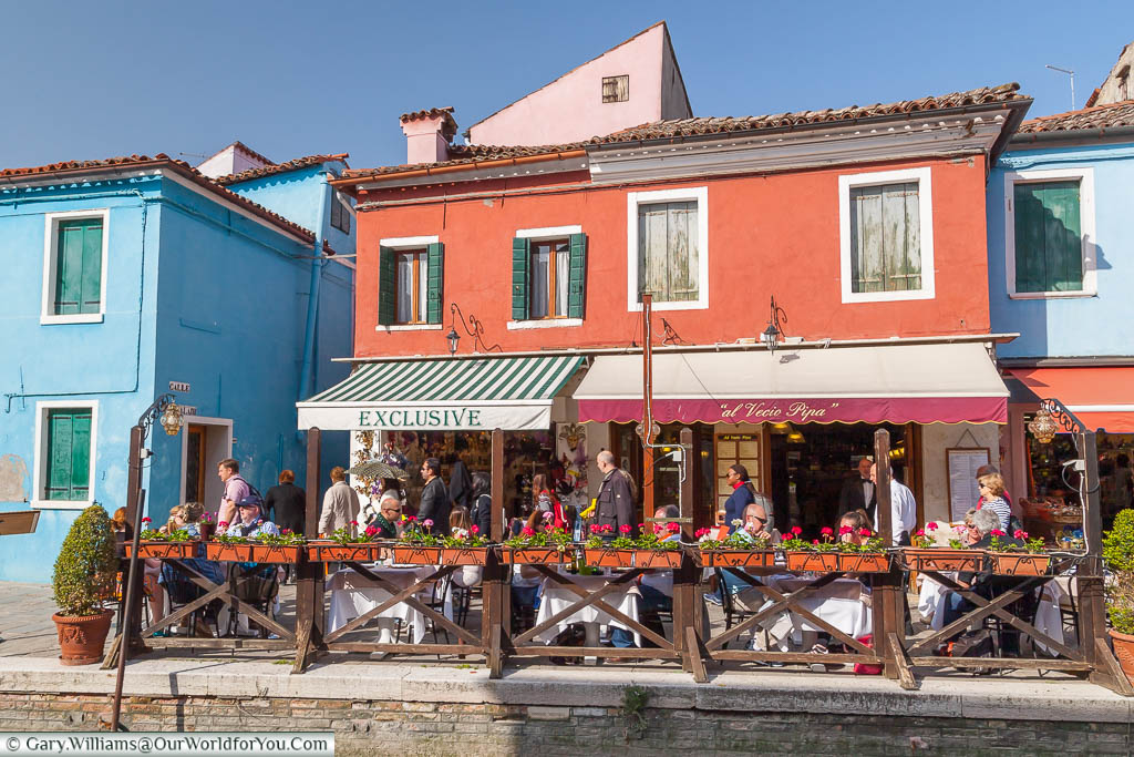 A handful of tables & chairs laid out canalside of a small, family-run, restaurant on the island of Burano