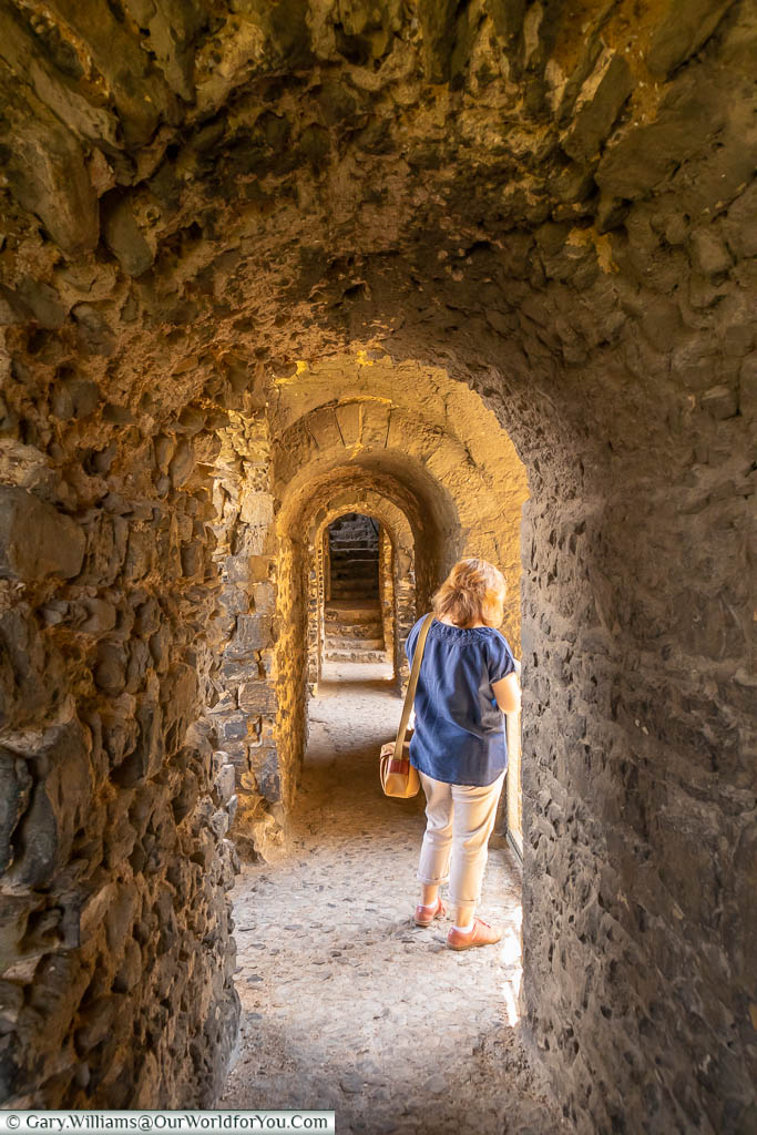 Janis with her back to us in one of the narrow stone corridors in Rochester castle