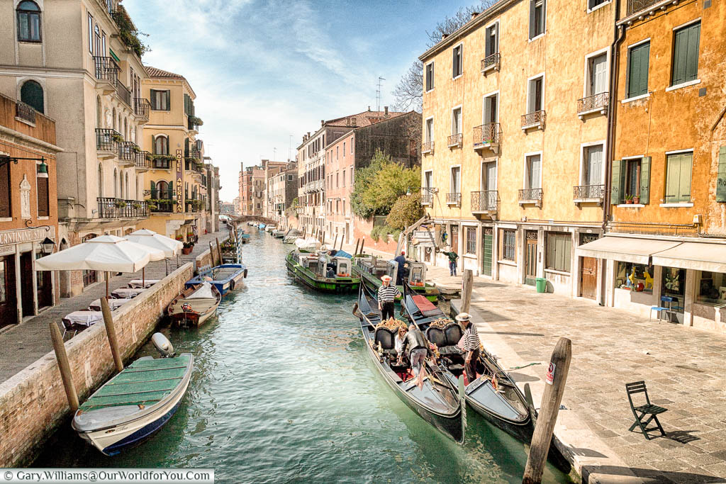 A couple joins a gondolier for a journey along the quiet canals of Venice.