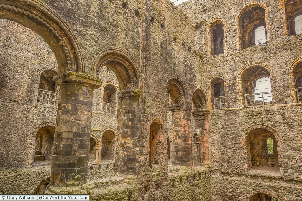 A thick stone diving wall in Rochester Castle, featuring large ornated arches for what would have been a grand hall.