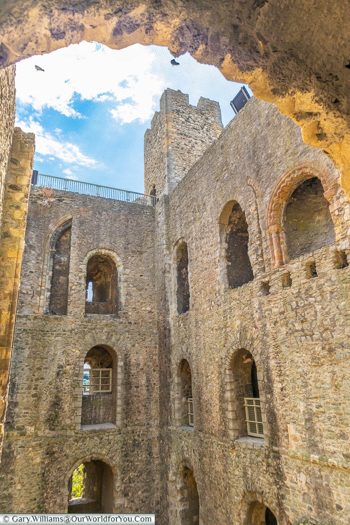 Looking through an archway, inside of the ruins of Rochester Castle, to one of the square corner towers