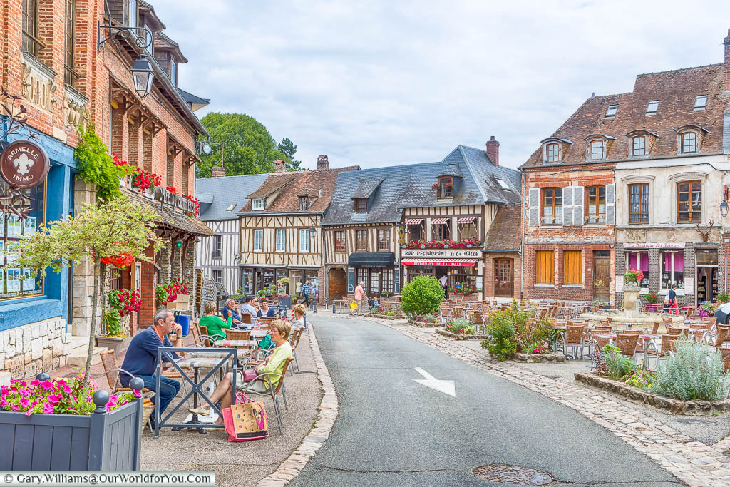 A street scene from the little Normandy village of Lyons-la-Forêt. People are sitting at tables and chairs outside the cafes in this quaint slide of French life.