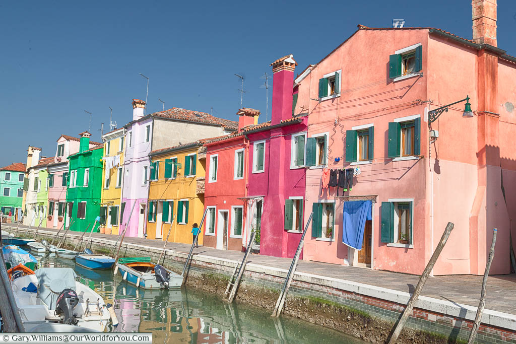 Laundry hanging from brightly coloured homes, packed together, along a canalside on the Island of Burano