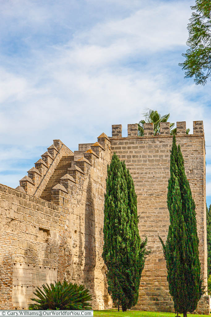 A stone tower in the walls of Jerez's Alcazar with stairs leading down to join the wall.