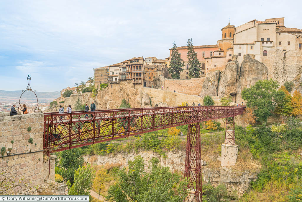 The maroon red wrought iron lattice bridge over a deep ravine to the hillside city of Cuenca with its hanging houses jutting from the rock face.
