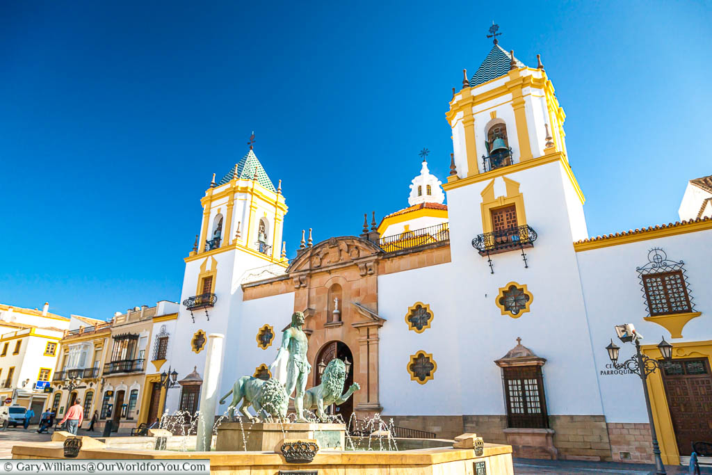 A fountain in the centre of Plaza del Socorro, in Ronda, adorned Hercules' verdigris brass statue with two lions. It stands in front of a white church with contrasting ochre features.