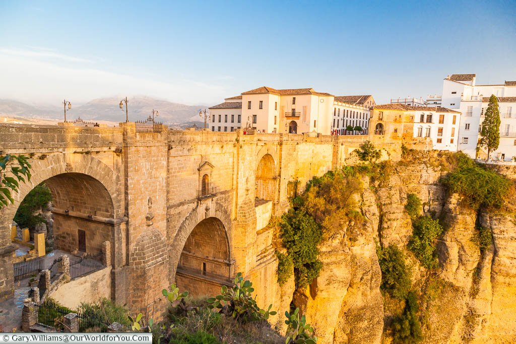 A substantial arched brick-built bridge, known as the 'Puente Nuevo', or New Bridge, in Ronda, Spain, constructed between two natural rockfaces over a deep chasm.