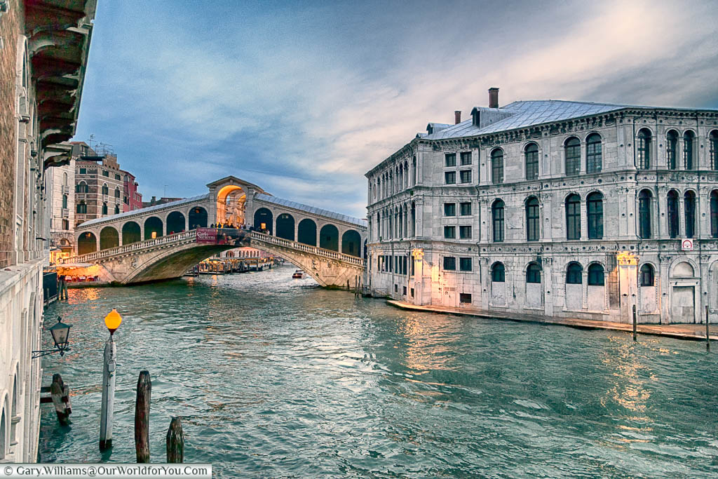 The Rialto Bridge across the Grand Canal of Venice at dusk as the lighting starts to come on.