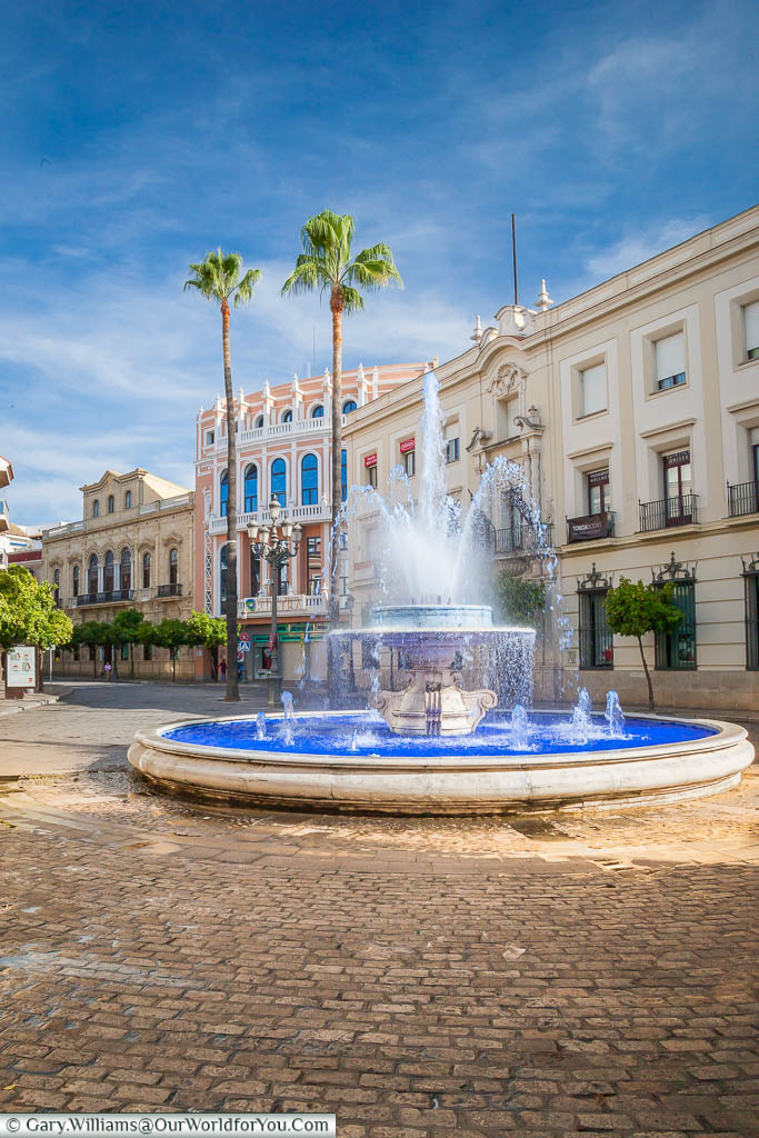 A fountain at the Rotonda de Los Casinos, filled with water dyed a deep blue, against the backdrop of beautiful Spanish classical architecture.