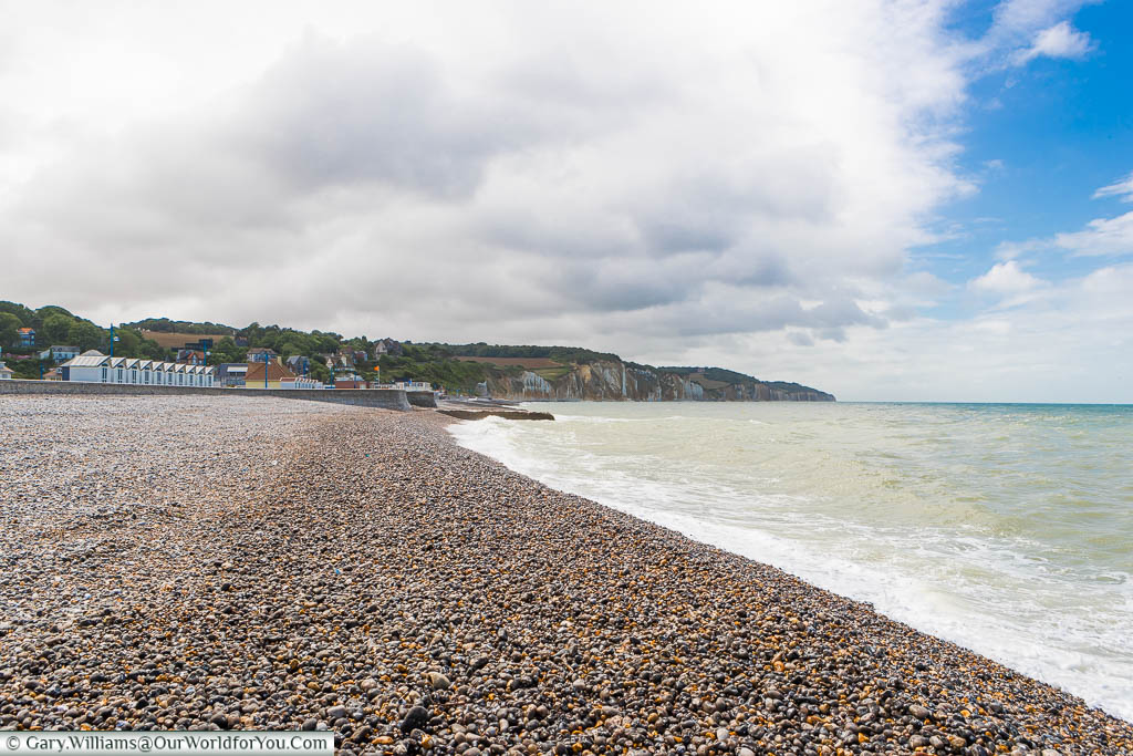 The Atlantic Ocean lapping against the shale beach at Hautot-sur-Mer with white chalk cliffs in the background.