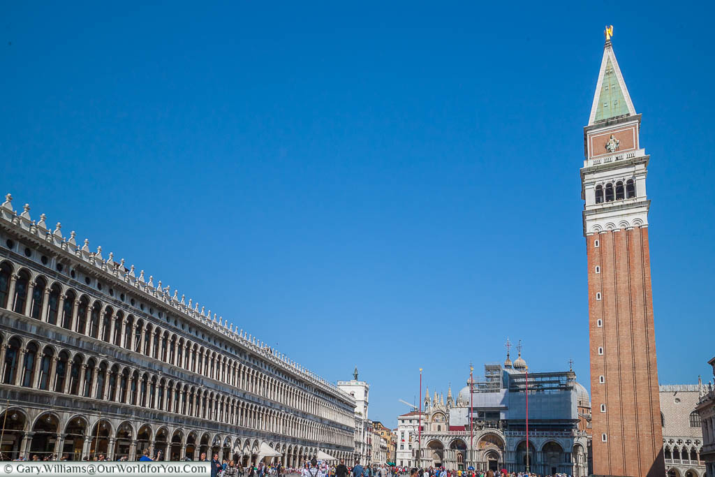 A view overlooking the bustling Piazza San Marco, with the colonnades to the left and the Campanile to the right with the Basilica di San Marco in the background