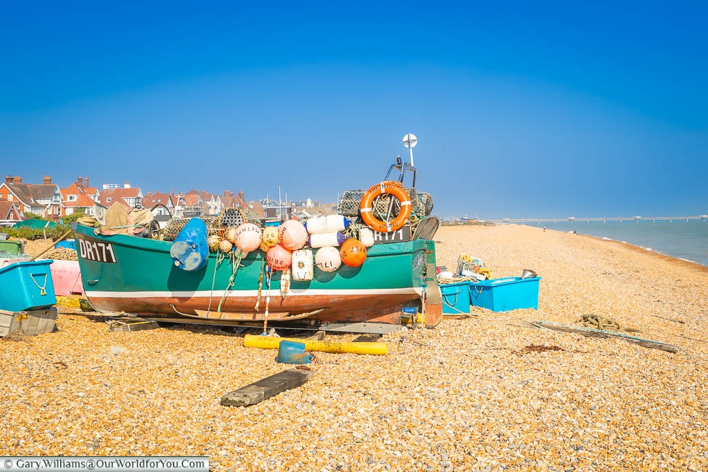 A small fishing boast surrounded by and covered in, floats and other fishing paraphernalia on the beach in Deal, Kent
