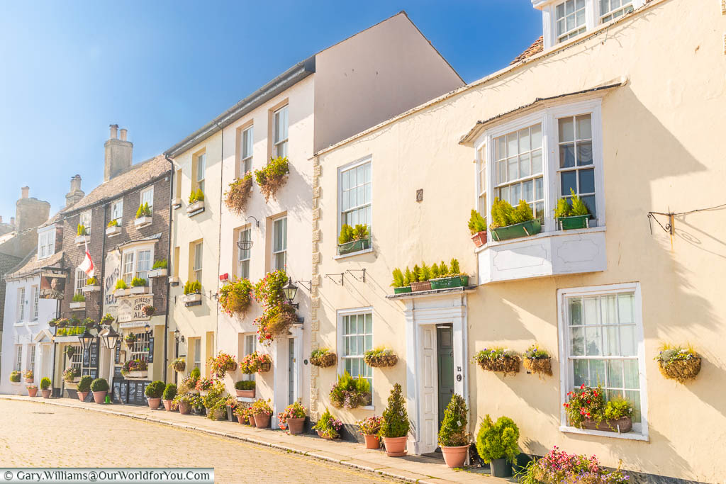 The pastel-coloured buildings decorated with potted plants & window baskets of beautiful Beach Street in Deal, Kent