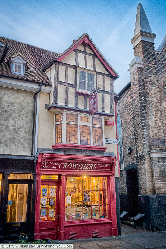 A shop with a red frontage in a historic building on the King's Mile in Canterbury