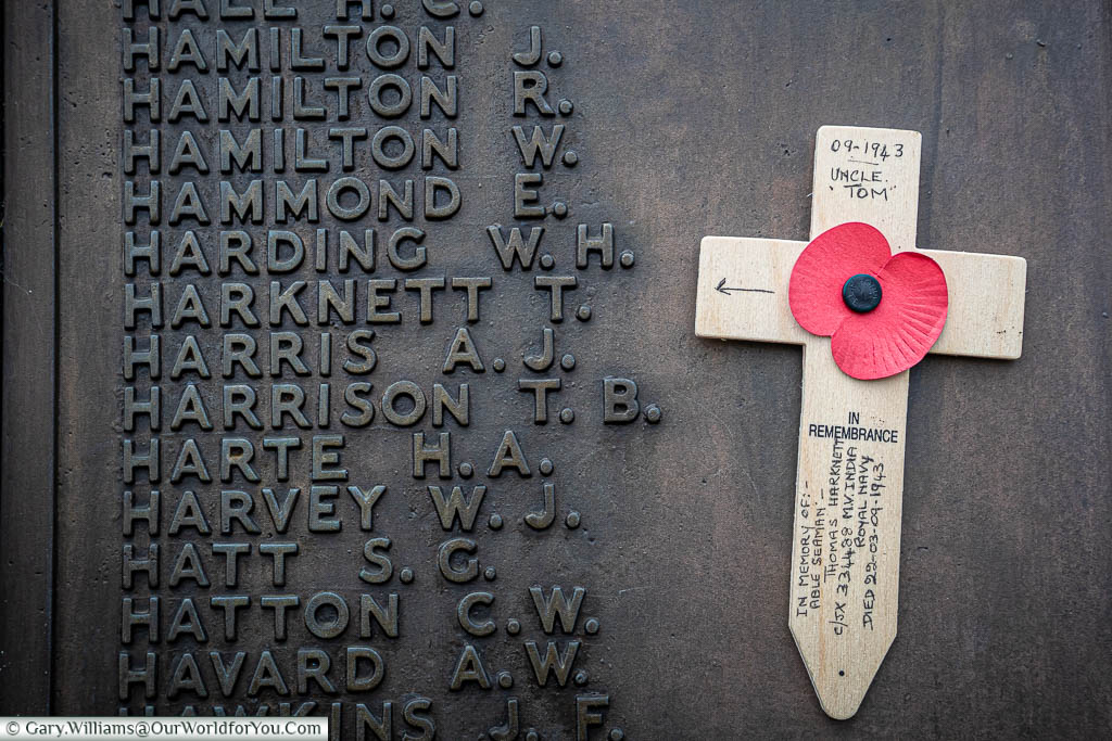 Attached to the brass plaque next to the inscription for Harknett T.A is a small wooden cross decorated with a Poppy, dedicated to Uncle Tom