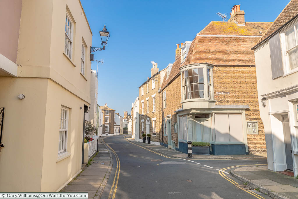 A view along the Deal's quaint Middle street with its soft pastel colours and brick buildings.