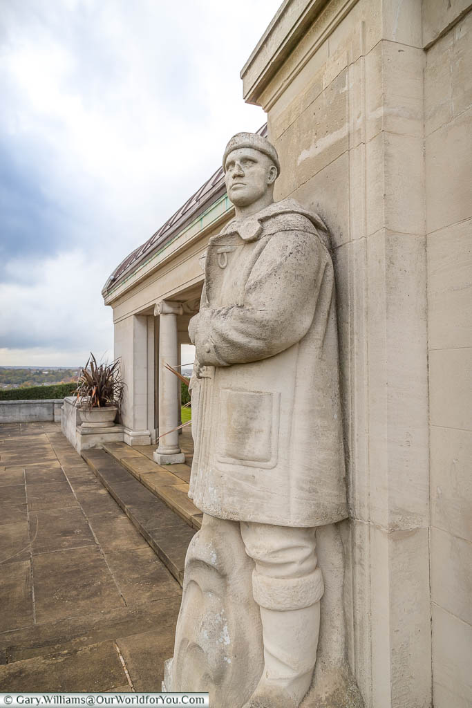 A stone sailor, wrapped in a heavy duffle coat, places as a lookout over Chatham from the Chatham Naval Memorial,