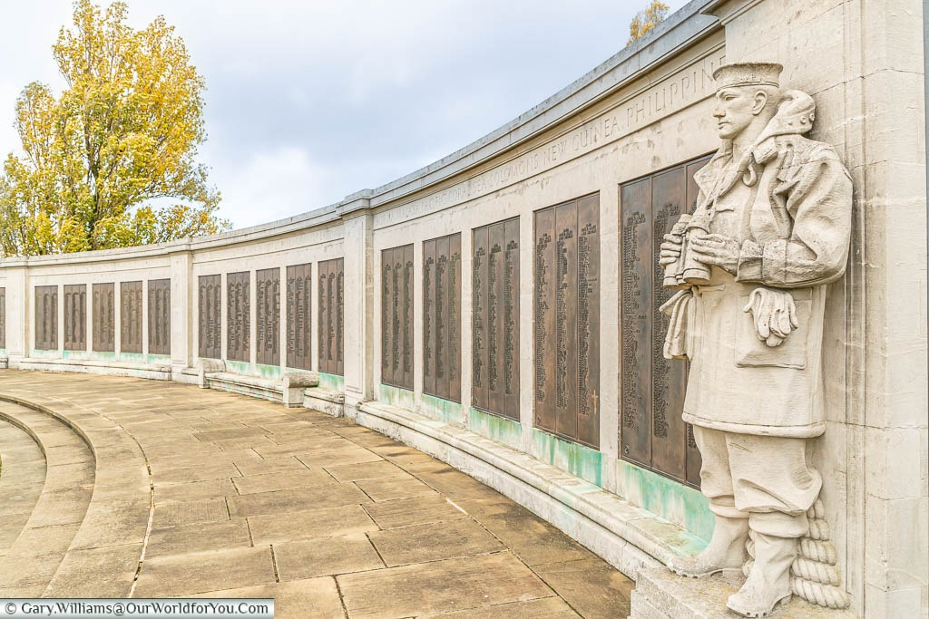 A stone seaman, holding binoculars, stands as a lookout at one end of a curved wall, adorned with brass plaques detailing the names & ranks of those lost at sea.