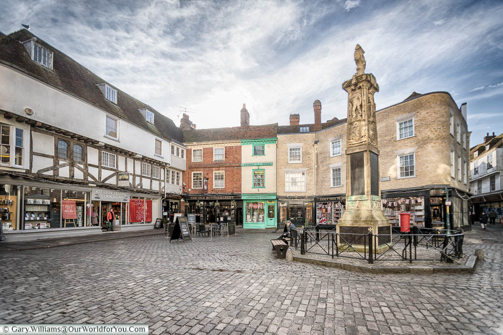 The cobbled pedestrian Buttermarket area of Canterbury, with the war memorial in the centre.