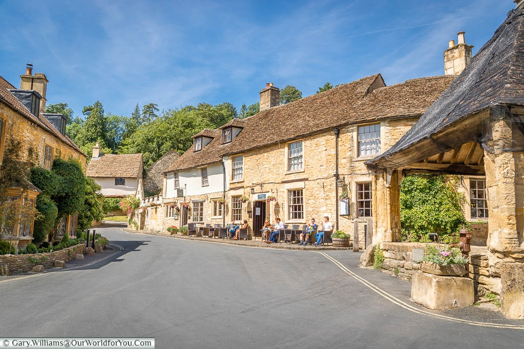 One side of the Market square of Castle Combe with the Castle Inn taking centre stage. A few lucky patrons are enjoying the summer sun whilst sitting outside