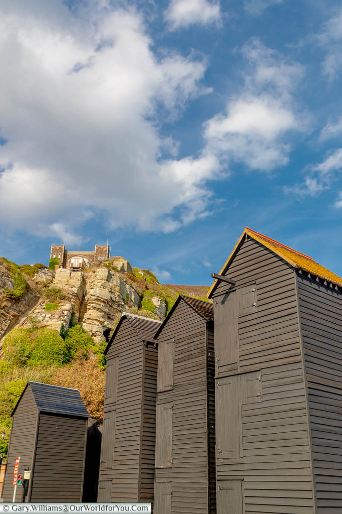 The wooden black weather-boarded net sheds in the Fishing Quarter of Hastings in the shadow of the East Hill funicular railway