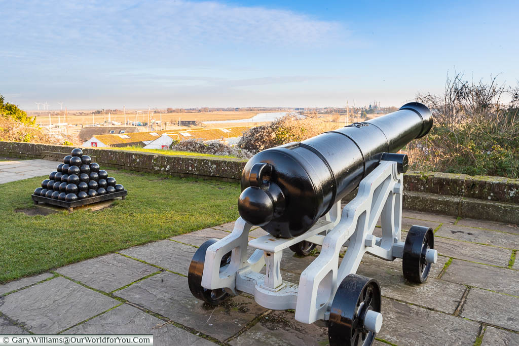 A cannon and cannonballs in the Gun Garden overlooking the River Rother as it flows past Rye