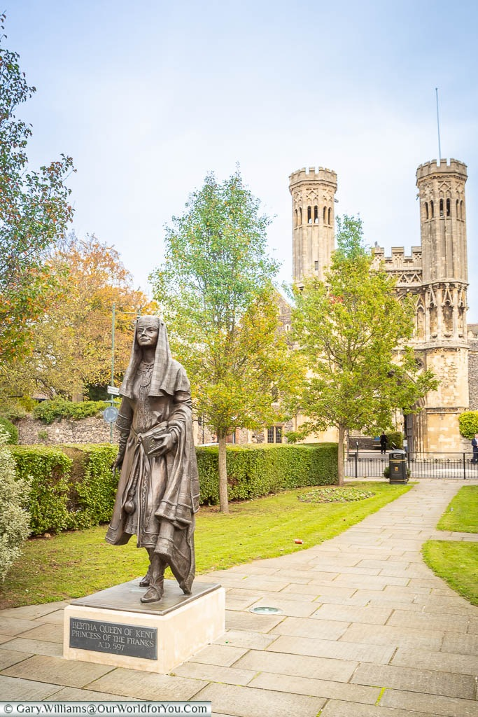 A brass statue to Queen Bertha of Kent in Lady Wootton's Green, with the gatehouse of St Augustine's Abbey in the background.