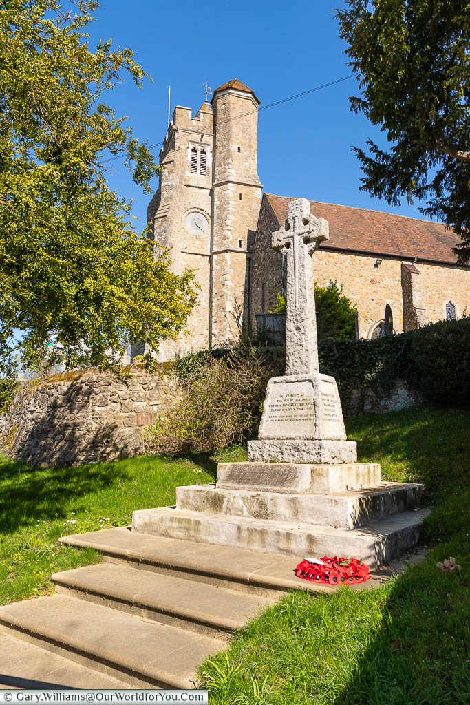 The stone cross war memorial in front of All Saints Church, Birling