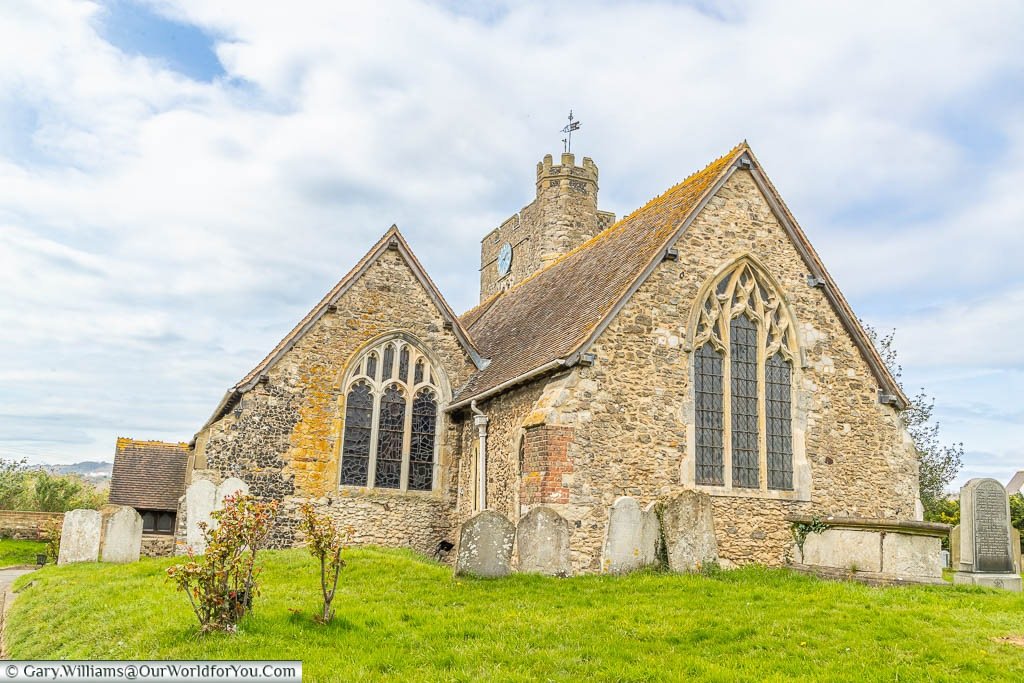 The small flintstone All Saints Church in Wouldhamas seen from the lychgate