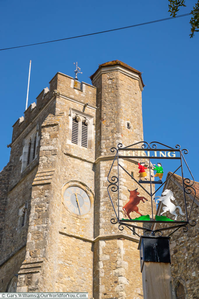 The iron village sign for Birling in front of the clock tower of All Saints Church, Birling