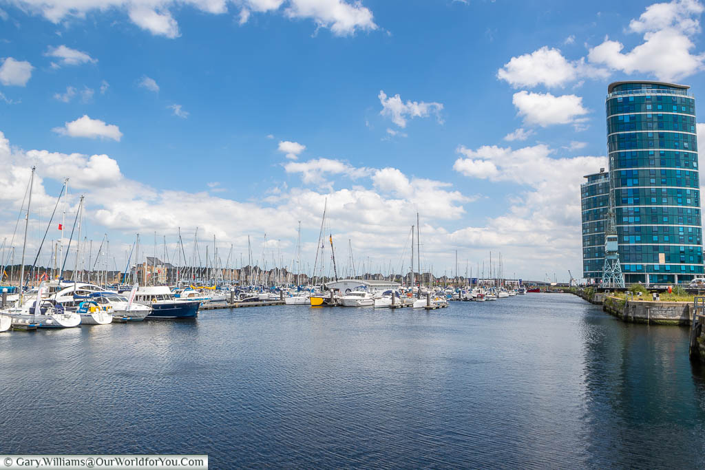 The thoroughly modern Chatham Marina filled with small boats and lined on one side by blue glass-fronted tower blocks on the edge of the docks