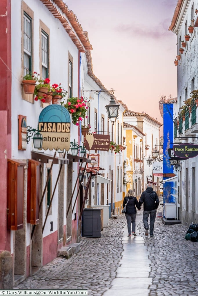 A couple walking along the main thoroughfare of old Óbidos town dusk.