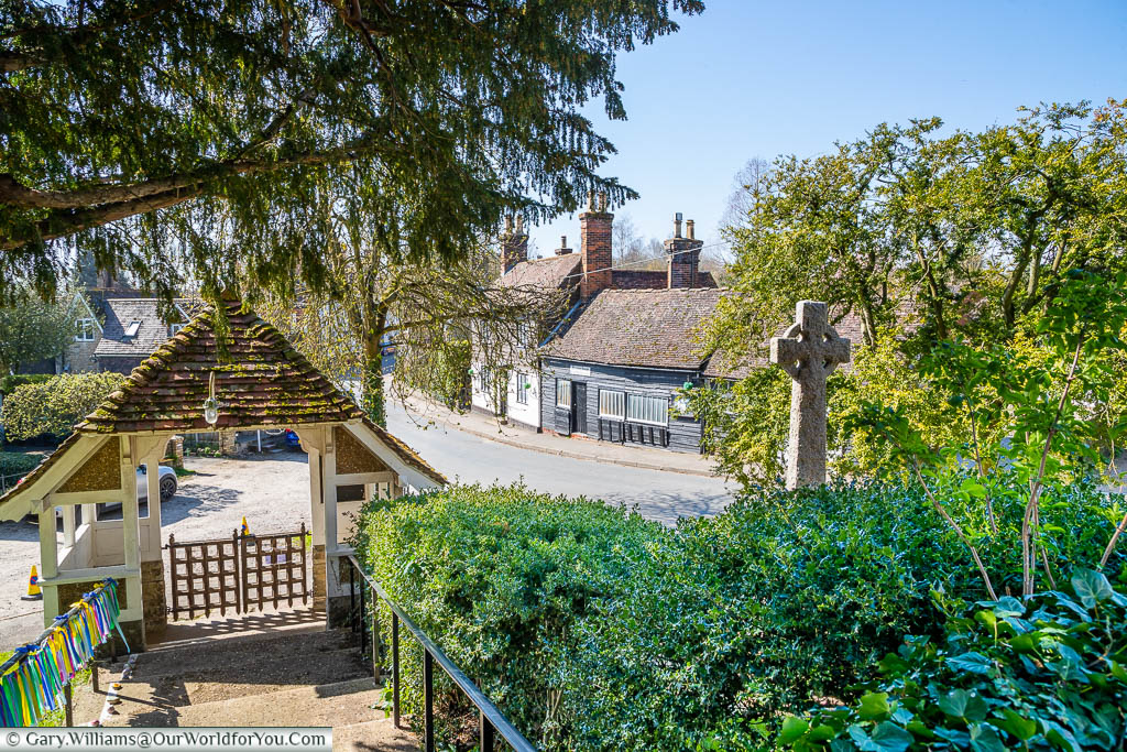 The view from steps of All Saints Church past the lychgate to the Old Forge alongside the main road through Birling, Kent