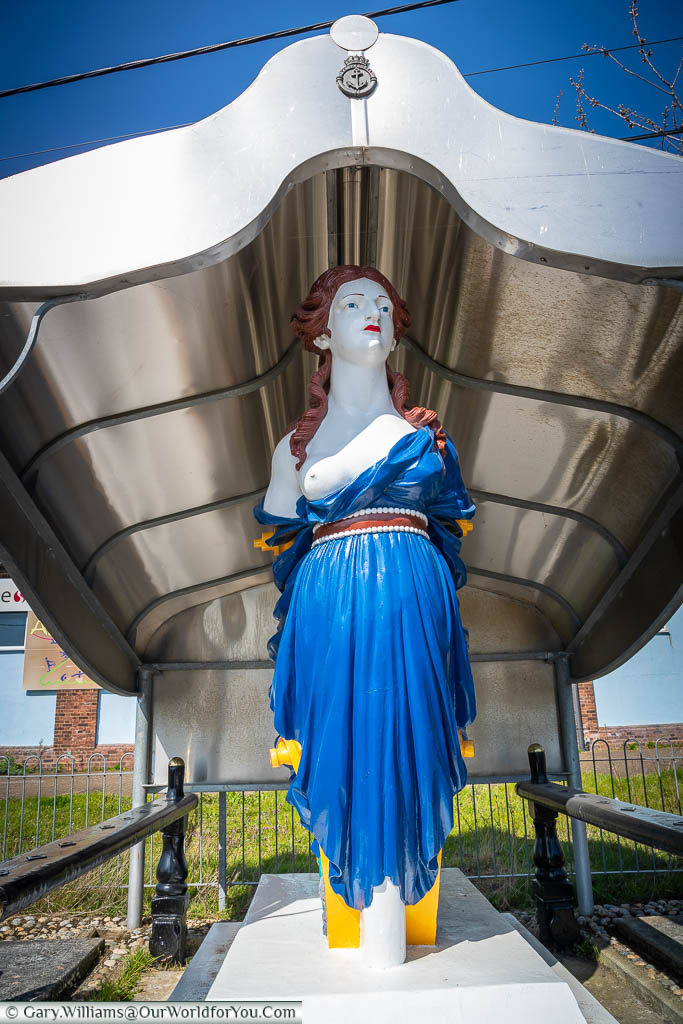 A brightly painted figurehead from HMS Arethusa of a red-headed woman, wearing a blue dress with a breast exposed