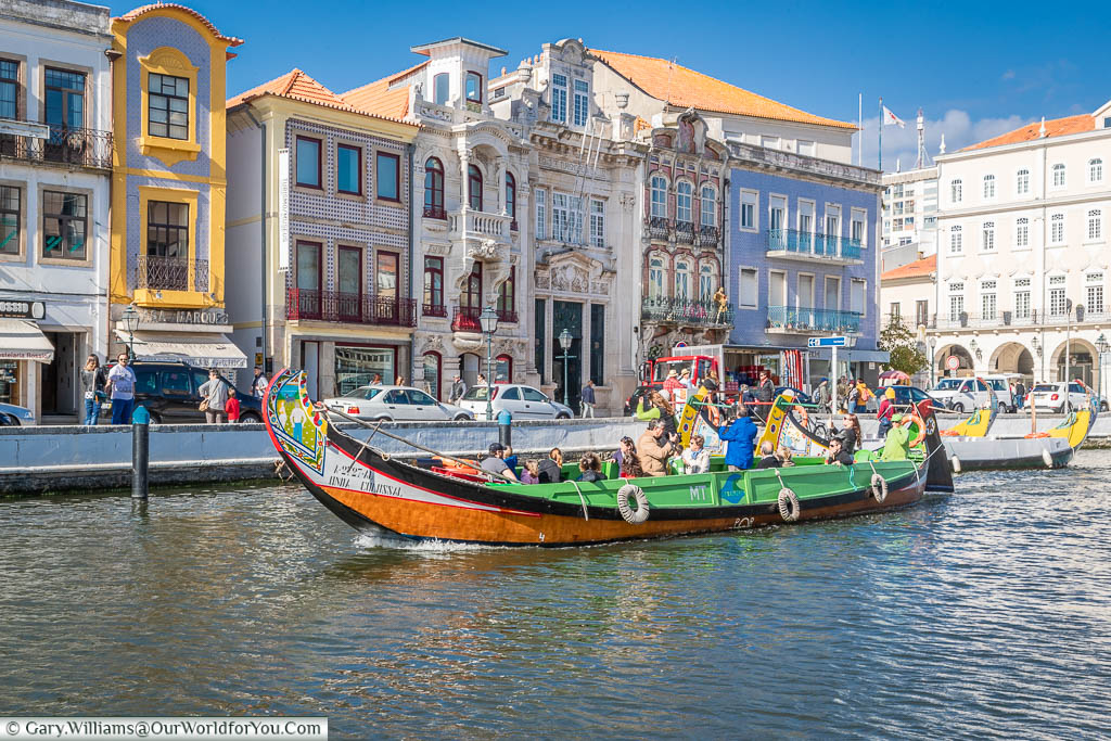 A colourful tourist Moliceiros boat in front of the beautiful classical architecture on the edge of the canal in Aveiro, Portugal