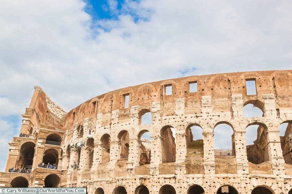 A view from outside the Colosseum under a blue skies & light clouds in Rome