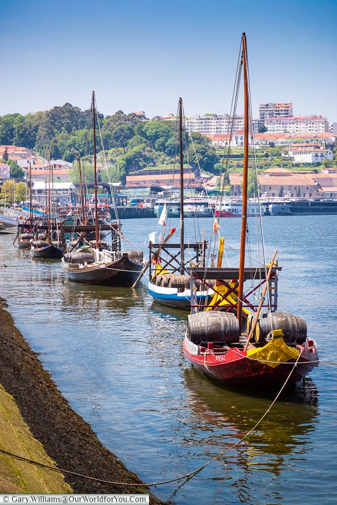 A row of traditional Rabelo sailing boats moored up on the south side of the Douro River in Porto, Portugal