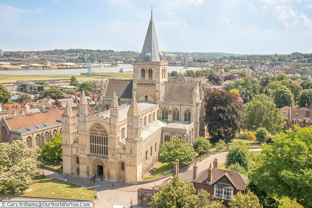 Looking down on Rochester cathedral from Rochester Castle with River Medway meandering through the landscape in the background.
