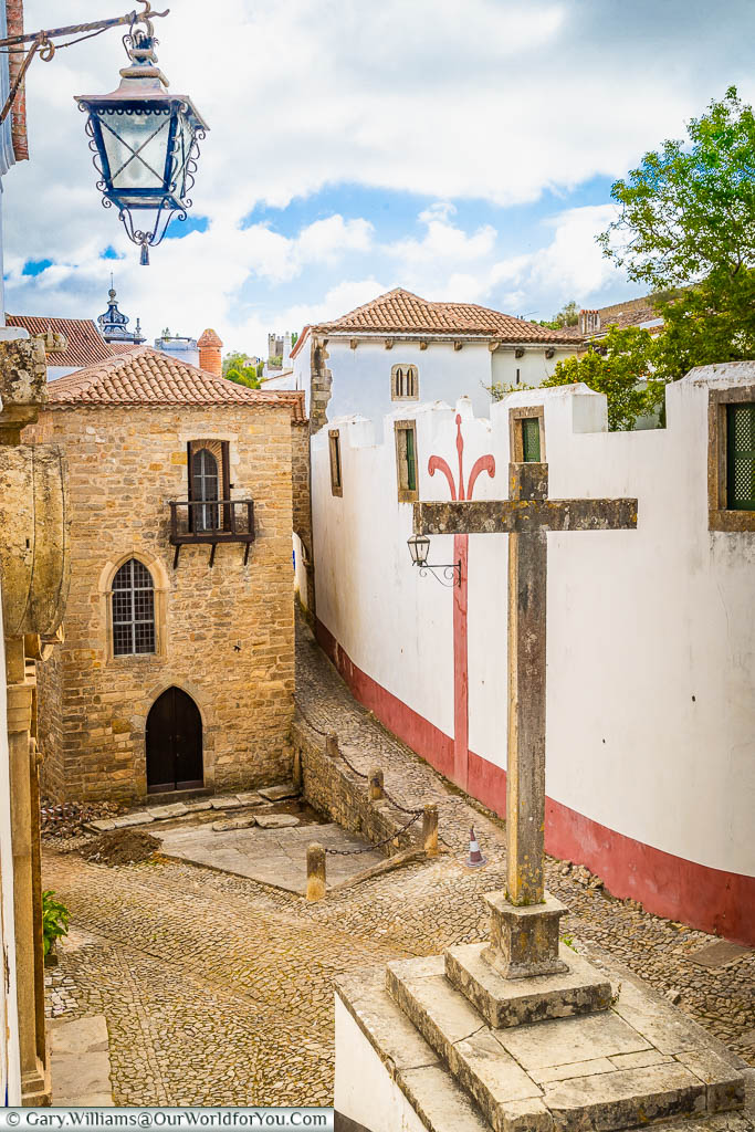 A stone cross in the centre of a tiny medieval square in the old town of Óbidos