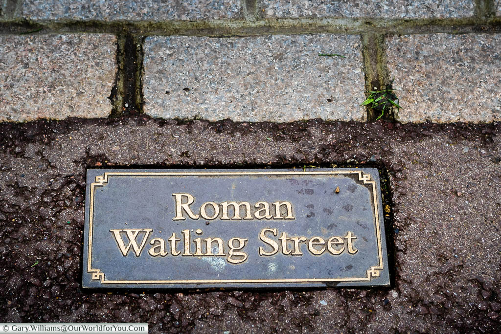 A metal plaque set in the path over Watling Street, the ancient Roman road from Dover to London