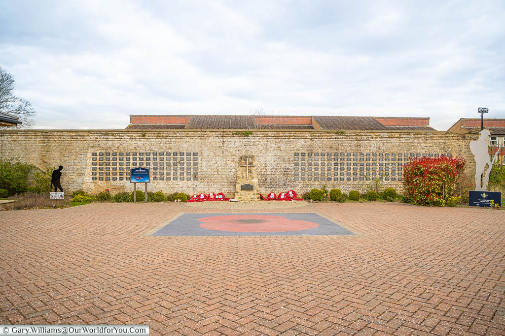 A poppy set into the square in front of the Wall of Honour in the memorial gardens of the Royal British Legion Villiage