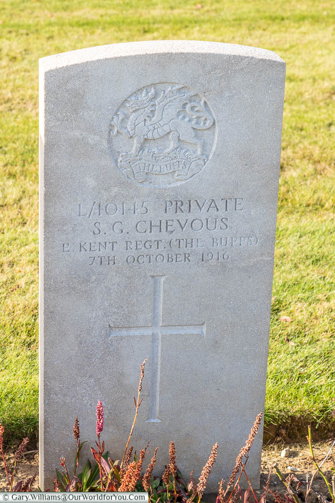 A Commonwealth War Graves Commission headstone for Sydney G Chevous of the Kent Buffs in the Bancourt British Cemetery, France
