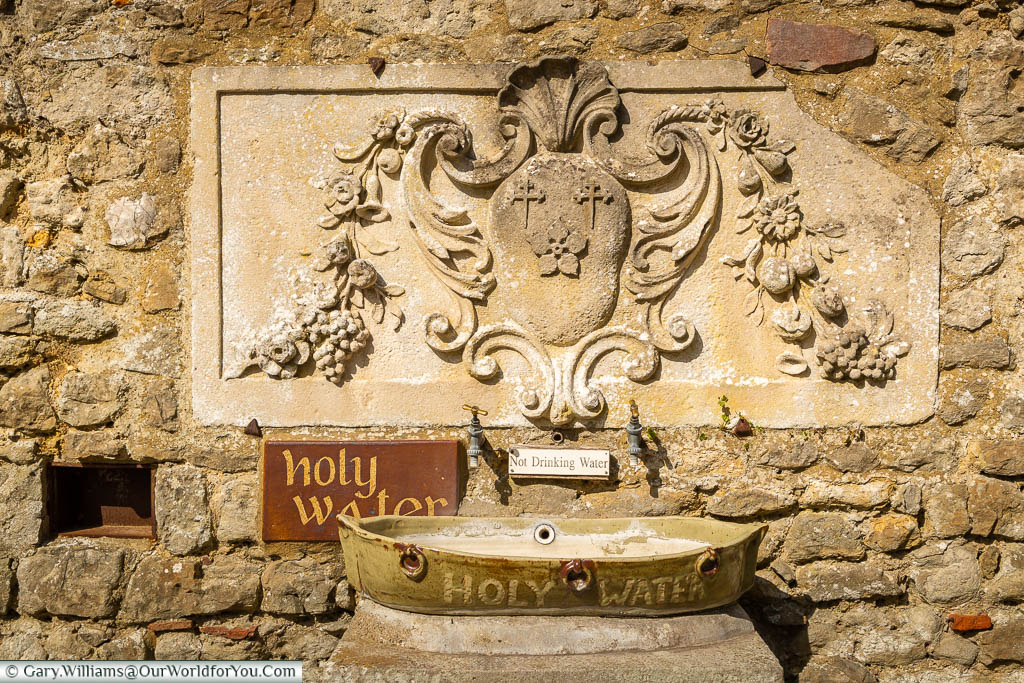 Two brass taps set in a stone wall that dispense holy water into a boat-shaped receptacle below.
