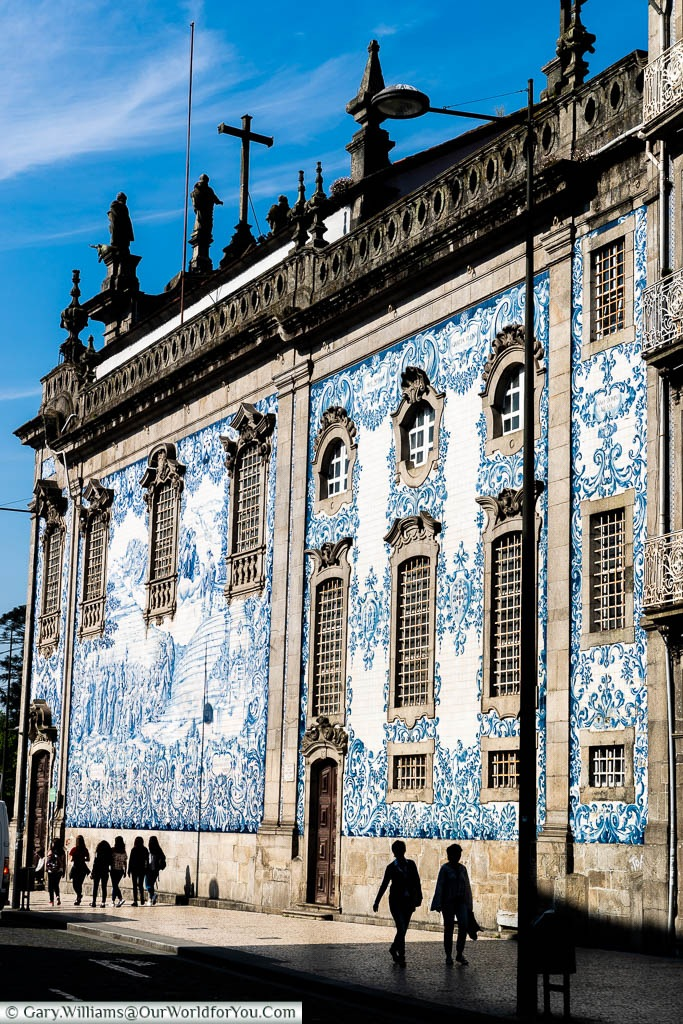 The silhouettes of people walking past blue-tiled baroque Igreja do Carmo in Porto, Portugal
