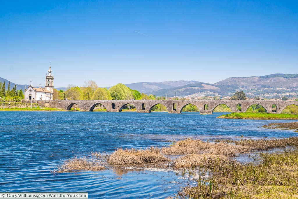 The view along the River Limia to the Roman bridge spanning it at Ponte de Lima in Northern Portugal