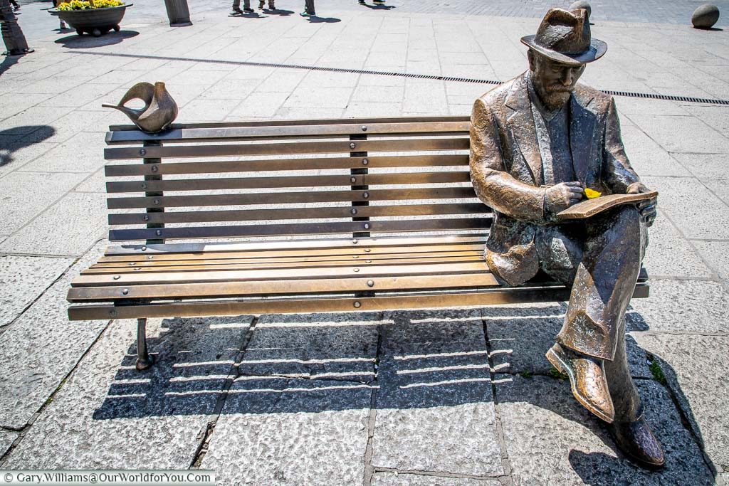 A bronze statue of Antonio Gaudi, seated on a bench, in front of a building he designed, in Leon, Spain.