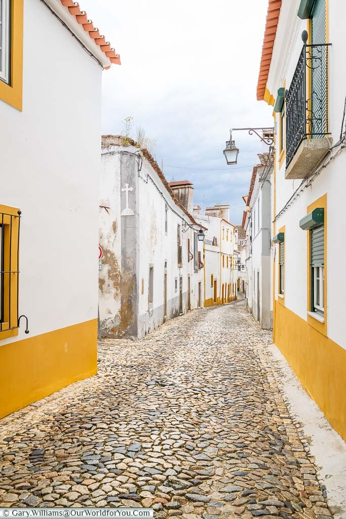 A narrow cobbled lane between white buildings, trimmed with a bold yellow, in the city of Évora, Portugal